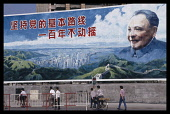 China, Guangdong Province, Shenzhen, Hoarding with portrait of Deng Xiaoping and vision of a modern city with text that reads Uphold the partys fundamental line - we will not waver in a hundred years.
