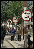 China, Tibet, Lhasa, Street signs lining the road with people waiting and a cyclist passing.