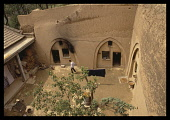 China, Shaanxi, Near Xian, Loess cave houses carved out of soft soil with man walking in courtyard.