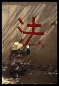 China, General, Man painting slogan in Chinese calligraphy onto a wall with red paint .