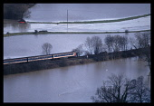 Climate, Weather, Flodding, Train going across the flooded plain of the River Ouse in Sussex, England.