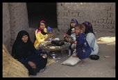 Egypt, Nile Valley, Family sat in courtyard eating food.