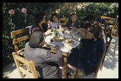 Greece, Pilion, Family having outdoor lunch around table.