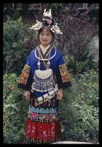 China, Guizhou , Kaili, Miao woman in traditional dress  portrait standing  full length.