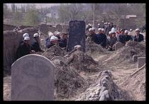 China, Gansu Province, Lanzhou, Praying in Muslim graveyard at end of Ramadan.