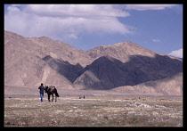 China, Xinjiang, Man with horse on the plateau near Taxkurgan on the  border with Pakistan.