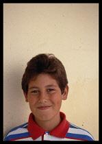 Greece, Ionian Islands, Corfu, Young teenage boy wearing red white and blue shirt.