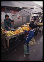China, Hunan, Huaihua, Boy buying oranges from a market vendor.