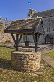 Ireland, County Leitrim, Dromahair, Parkes Castle, Wishing well in the courtyard with the castle itself in the background.