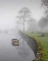 Ireland, County Sligo, Sligo town, Doorly Park, Boat on the River Garavogue on a foggy winter's morning.