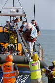 England, Kent, Dungeness, RNLI, helping migrants who have crossed the channel onto the beach.