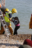 England, Kent, Dungeness, RNLI, helping migrants who have crossed the channel onto the beach, Susina 5yrs old and traveled with her mum from Eritrea.