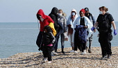 England, Kent, Dungeness, Immigration officers escorting recently landed migrants to be processed, Susina 5yrs old and traveled with her mum from Eritrea.