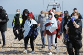 England, Kent, Dungeness, Immigration officers escorting recently landed migrants to be processed.