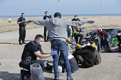 England, Kent, Dungeness, Migrants being searched by immiragtion officers on the beach.
